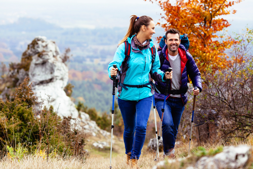 Woman and man hiking in mountains with backpacks